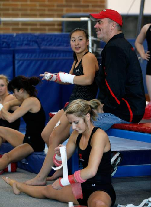 Al Hartmann  |  Tribune file photo Ute gymnastics coach Greg Marsden talks with team members as they tape their wrists before a workout to prepare for NCAA regionals at the Huntsman Center.