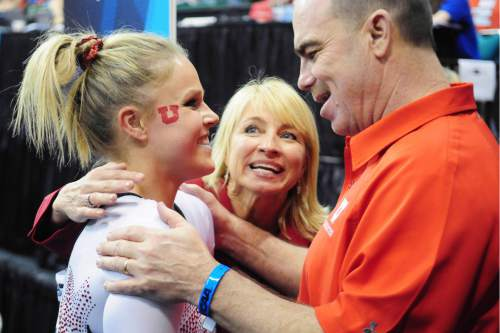 (Jason Miller file photo)  University of Utah senior Gael Mackie, left, gets a congratulations from co-head coaches Megan Marsden, center, and Greg Marsden, right, after Mackie's uneven parallel bars routine at the 2011 Women's NCAA Gymnastics Championship Team Finals on April 16, in Cleveland, Ohio.