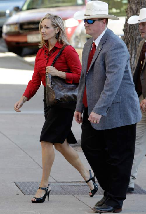 A law enforcement officer, right, escorts Rebecca Musser, left, a former member of the Fundamentalist Church of Jesus Christ of Latter Day Saints and a witness for the prosecution as she arrives at Tom Green County Courthouse for the sentencing phase of the Warren Jeffs sexual assault trial Friday Aug. 5, 2011, in San Angelo, Texas.  (AP Photo/Tony Gutierrez)