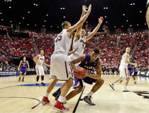 Weber State's Joel Bolomboy, right, is double-teamed by Arizona's Kaleb Tarczewski, left, and Aaron Gordon during the second half in a second-round game in the NCAA college basketball tournament Friday, March 21, 2014, in San Diego. (AP Photo/Gregory Bull)