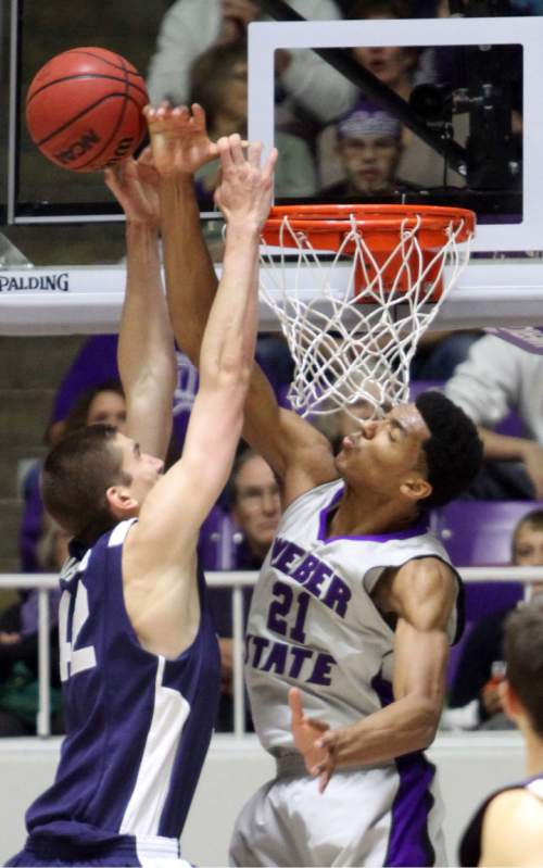 Rick Egan  | The Salt Lake Tribune   Weber State Wildcats forward/center Joel Bolomboy (21) blocks a shot by Brigham Young Cougars center Ian Harward (42) in basketball action, BYU vs. Weber State, in Ogden, Saturday, December 15, 2012.