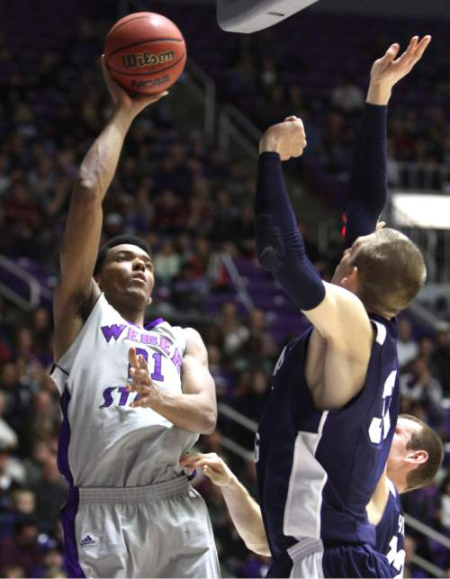 Rick Egan  | The Salt Lake Tribune   Weber State Wildcats forward/center Joel Bolomboy (21) shoots over Brigham Young Cougars guard Cory Calvert (23) in basketball action, BYU vs. Weber State, in Ogden, Saturday, December 15, 2012.