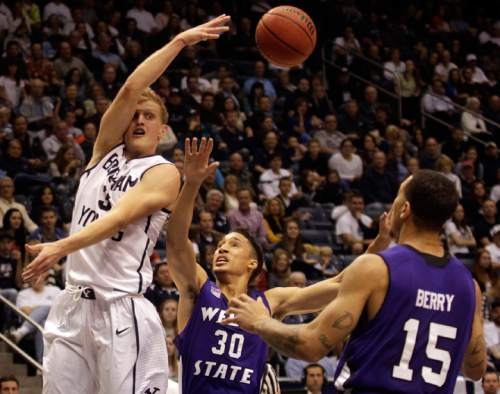 Brigham Young's Tyler Haws (3) passes the ball as Weber State's Jeremy Senglin (30) and Davion Berry (15) defend uring an NCAA college basketball game Friday, Nov. 8, 2013, in Provo, Utah. (AP Photo/Daily Herald, James Roh)