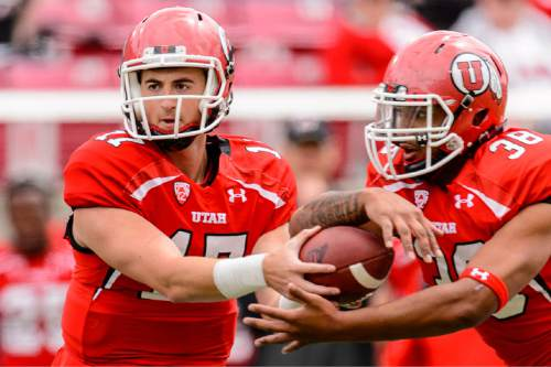 Trent Nelson  |  The Salt Lake Tribune Quarterback Conner Manning hands off the ball to Tani Leha'uli at the Utah Football Red & White game in Salt Lake City, Saturday April 25, 2015.