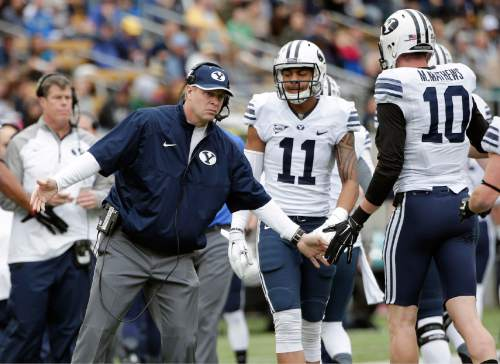 BYU head coach Bronco Mendenhall celebrates with players after a touchdown against California during the first half of an NCAA college football game, Saturday, Nov. 29, 2014, in Berkeley, Calif. (AP Photo/Marcio Jose Sanchez)