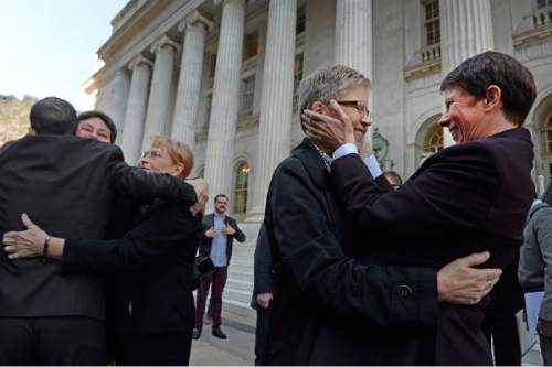 DENVER, CO. - APRIL 10:  Utah Plantiffs Laurie Wood, fourth from left, embraces her partner, Kody Partridge, right, as fellow plaintiffs, Moudi Sbeity, left, hugs Kate Call and Kate's partner, Karen Archer, third from left, outside of the Byron White U.S. Courthouse after a press conference Thursday morning, April 10, 2014 after the U.S. Court of Appeals for the 10th Circuit listened to oral arguments on the gay marriage ban in Utah. (Photo By Andy Cross / The Denver Post)