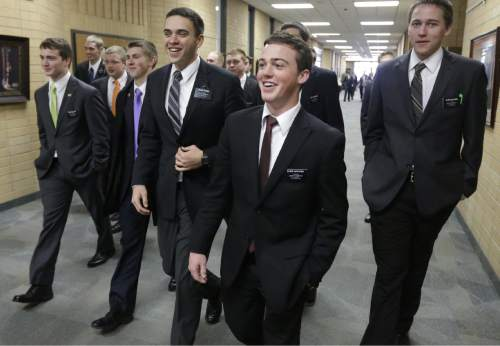 FILE - In this Jan. 8, 2013, file photo, Mormon missionaries walk through the halls at the Missionary Training Center in Provo, Utah. A record number of young Mormons signed up for missions after church leaders lowered the minimum age in 2012, but new figures show the onslaught of proselytizing Latter-day Saints didn't lead to an equally dramatic spike in converts. (AP Photo/Rick Bowmer, File)