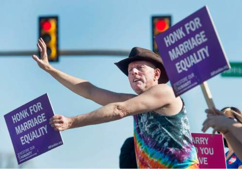 Steve Griffin  |  The Salt Lake Tribune  John Wilkes, of Murray, participates in a honk and wave to support same-sex marriage arguments at the U.S. Supreme Court, outside Piper Down Pub near 1500 South and State Street in Salt Lake City, Tuesday, April 28, 2015.