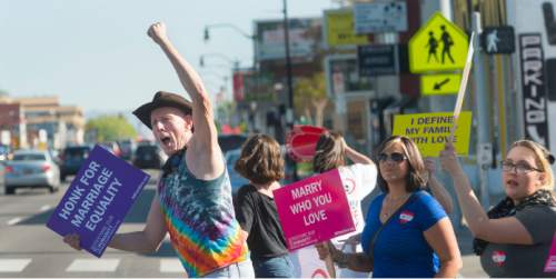 Steve Griffin  |  The Salt Lake Tribune  John Wilkes, of Murray, left, pumps his fist as he participates in a honk and wave to support same-sex marriage arguments at the U.S. Supreme Court, outside Piper Down Pub near 1500 South and State Street in Salt Lake City, Tuesday, April 28, 2015.