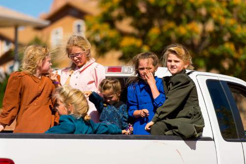 Trent Nelson  |  The Salt Lake Tribune Young girls ride in the back of a truck in Hildale, Thursday September 25, 2014.