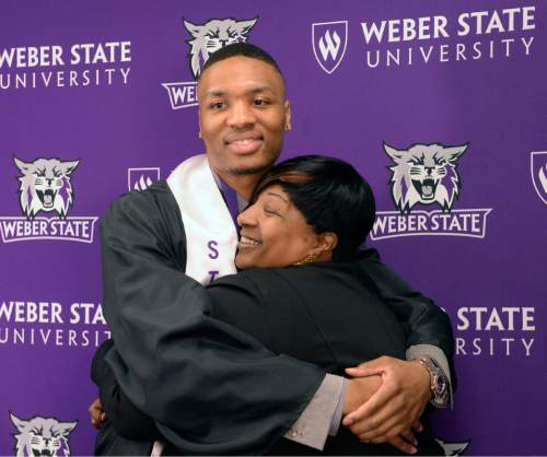 Al Hartmann  |  The Salt Lake Tribune Damian Lillard, point guard for the Portland Trail Blazers, center, hugs his mother Gina Johnson at a press conference at the Dee Events Center before he received his diploma at the Weber State commencement ceremony Friday May 1.    Lillard is graduating with a degree in professional sales. He  was six credits shy of graduating when he was drafted in 2012, but polished off his classes in the offseason.