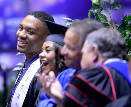 Al Hartmann  |  The Salt Lake Tribune Damian Lillard, point guard for the Portland Trail Blazers, and Shaquille Heath, student graduation speaker watch procession of graudates fill the Dee Event Center Friday May 1.  Lillard later addressed fellow Weber State University graduates.  Lillard is graduating with a degree in professional sales. He  was six credits shy of graduating when he was drafted in 2012, but polished off his classes in the offseason.