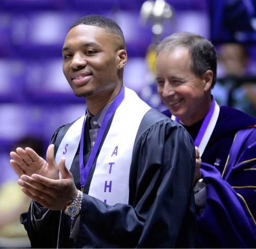 Al Hartmann  |  The Salt Lake Tribune Damian Lillard, point guard for the Portland Trail Blazers, applauds fellow Weber State graduates at the Dee Event Center Friday May 1. WSU President Dr. Charles A. Wight introduces him. Lillard laterspoke to Weber State University graduates.  Lillard is graduating with a degree in professional sales. He  was six credits shy of graduating when he was drafted in 2012, but polished off his classes in the offseason.