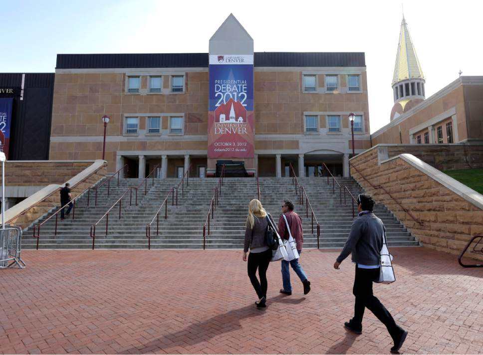 Workers walk outside the Magness Arena at the Daniel L. Ritchie Center for Sports and Wellness, site of Wednesday's presidential debate, on the campus of the University of Denver, Monday, Oct. 1, 2012, in Denver. (AP Photo/Charlie Neibergall)