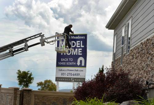 Scott Sommerdorf   |  The Salt Lake Tribune A workman erects a set of signs for new homes in the Ruston Meadows Development near 4017 West Great Neck Drive 11300 South in South Jordan, Wednesday, May 20, 2015.  South Jordan has beat out Taylorsville as Utah's 10th most populous city, after Taylorsville held the 10th spot for the prior four years.