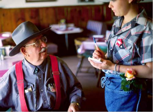 (Courtesy J. Sharee Jones) A patron and waitress chat at Dick's Cafe circa 1999. The flower was given to the waitress that morning by regular customers.