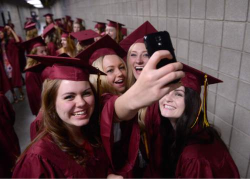 Al Hartmann |  The Salt Lake Tribune Lone Peak High School graduates celebrate and take a group selfie waiting in the corridor of the UCUU Events Center before marching in procession for school commencement Thursday May 28, 2015.