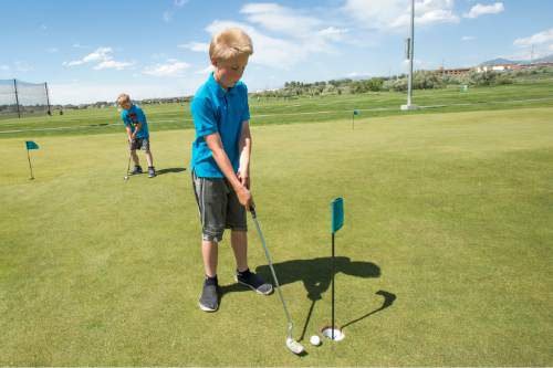 Rick Egan  |  The Salt Lake Tribune  Pierson Thomas, 8 and Hunter Thomas, 10, practice their putting at Mulligans, Monday, June 1, 2015.