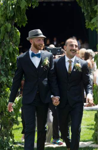 Steve Griffin  |  The Salt Lake Tribune Derek Kitchen and Moudi Sbeity, the lead plaintiffs from the landmark Utah case that legalized same-sex marriage, hold hands as the walk up the aisle after getting married in a large public ceremony at the Gallivan Center Plaza in Salt Lake City, Sunday, May 24, 2015.