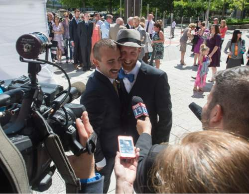 Steve Griffin  |  The Salt Lake Tribune Derek Kitchen and Moudi Sbeity, the lead plaintiffs from the landmark Utah case that legalized same-sex marriage, hug as they make a statement to the media following their public marriage ceremony at the Gallivan Center Plaza in Salt Lake City, Sunday, May 24, 2015.