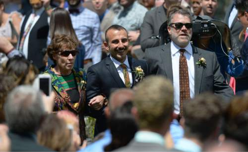 Steve Griffin  |  The Salt Lake Tribune Peggy Tomsic and Jim Magleby walk Moudi Sbeity, center, down the aisle during Sbeity and Derek Kitchen's marriage ceremony at the Gallivan Center Plaza in Salt Lake City, Sunday, May 24, 2015. Tomsic and Magleby were the attorneys for Sbeity and Kitchen who were the lead plaintiffs from the landmark Utah case that legalized same-sex marriage.