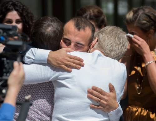 Steve Griffin  |  The Salt Lake Tribune   Moudi Sbeity, center, hugs Kody Partridge and Laurie Wood following his marriage to Derek Kitchen at the Gallivan Center Plaza in Salt Lake City, Sunday, May 24, 2015. The couples were plaintiffs from the landmark Utah case that legalized same-sex marriage get married in a large public ceremony