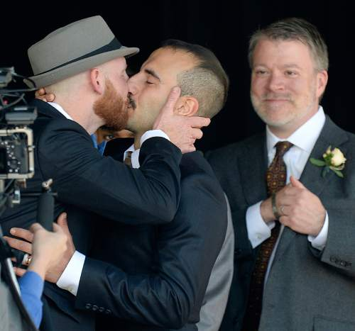 Scott Sommerdorf   |  The Salt Lake Tribune Derek Kitchen, left, and Moudi Sbeity, kiss after they were pronounced husband and husband. Kitchen and Sbeity, the lead plaintiffs from the landmark Utah case that legalized same-sex marriage, got married in a large public ceremony in the Gallivan Center Plaza, Sunday, May 24, 2015.