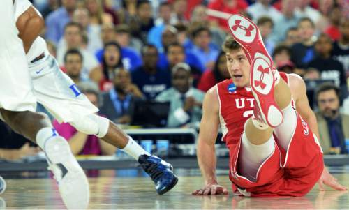 Steve Griffin  |  The Salt Lake Tribune  Utah Utes center Dallin Bachynski (31) falls tot he court as he goes for a loose ball during second half action in the University of Utah versus Duke University Sweet 16 game in the 2015 NCAA Men's Basketball Championship Regional Semifinal game at NRG Stadium in Houston, Friday, March 27, 2015.