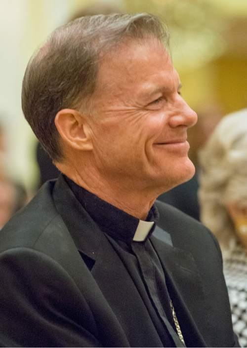 Rick Egan  |  The Salt Lake Tribune  Archbishop John C. Wester smiles as he listens to the Rev. Scott B. Hayashi, dishop of the Episcopal Diocese of Utah during a reception at the Little America, Sunday, May 31, 2015.