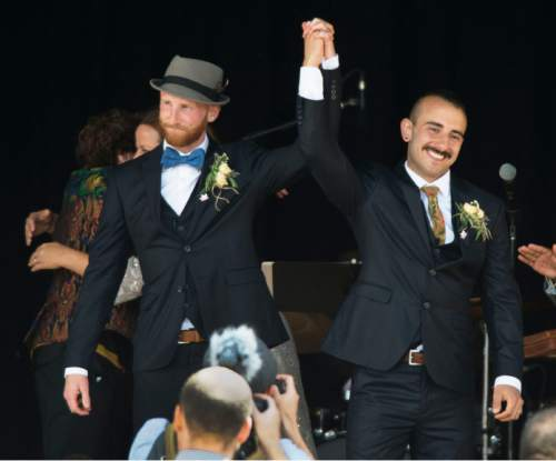 Steve Griffin  |  The Salt Lake Tribune Derek Kitchen and Moudi Sbeity, the lead plaintiffs from the landmark Utah case that legalized same-sex marriage, hold their hands up after getting married in a large public ceremony at the Gallivan Center Plaza in Salt Lake City, Sunday, May 24, 2015.