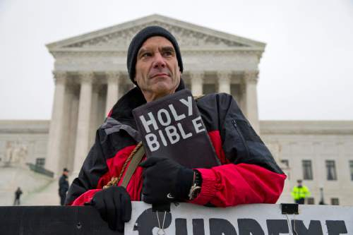 FILE - In this Jan. 15, 2014 file photo, Alan Hoyle, of Lincolnton, N.C., stands outside the Supreme Court in Washington, Wednesday, Jan. 15, 2014, where the court heard arguments on a state of Massachusetts law setting a 35-foot (10 meter) protest-free zone outside abortion clinics. Abortions have declined in states where new laws make it harder to have them -but they've also waned in states where abortion rights are protected, an Associated Press survey finds. Nearly everywhere, in red states and blue, abortions are down since 2010. (AP Photo/ Evan Vucci, File)