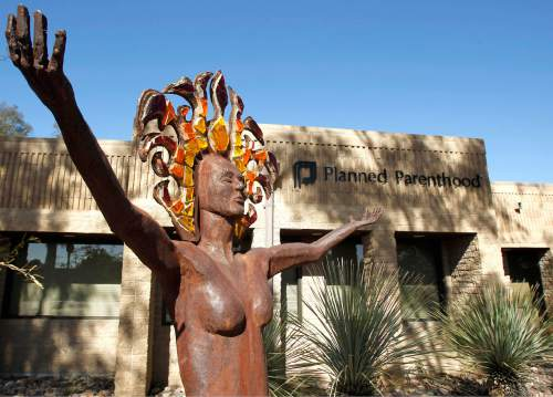 FILE - In this Jan. 23, 2011 photo, a statue representing women's empowerment stands in front of a Planned Parenthood facility in Tucson, Ariz. Abortions have declined in states where new laws make it harder to have them - but they've also waned in states where abortion rights are protected, an Associated Press survey finds. Nearly everywhere, in red states and blue, abortions are down since 2010. Explanations vary. Abortion-rights advocates attribute it to expanded access to effective contraceptives and a drop in unintended pregnancies.  (AP Photo/Ross D. Franklin, File)