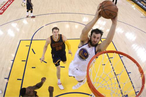 Golden State Warriors center Andrew Bogut (12) dunks against Cleveland Cavaliers center Timofey Mozgov (20) during the second half of Game 1 of basketball's NBA Finals in Oakland, Calif., Thursday, June 4, 2015. The Warriors won 108-100 in overtime. (Ezra Shaw/Getty Images Pool via AP)