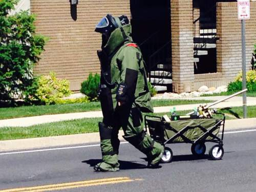 (Courtesy of Cottonwood Heights Police Department)  A member of the Unified Fire Authority bomb squad attempts to remove a suspected explosive device in Cottonhoow Heights on Monday, June 8, 2015.