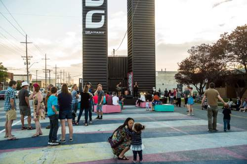 Chris Detrick  |  The Salt Lake Tribune Patrons enjoy the performance of Nick Nervous with Caiti and Kelsi Fadness during Granary Row pop up street festival Friday June 5, 2015. The placement of the shipping containers -- in the middle of 700 South between 300 and 400 West -- was a solution the community developed during brain-storming sessions about the area. Members wanted a way to break up the wide streets -- considered an asset and a liability when planning -- and create a more welcoming pedestrian element. The Granary Row pop-up festival is designed to celebrate that gritty, urban personality.