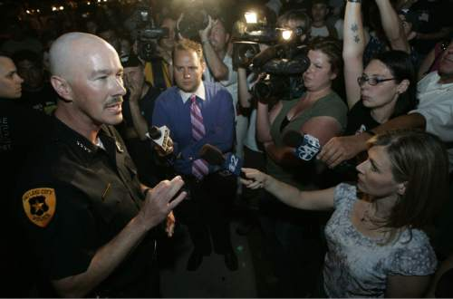 |  Tribune File Photo  Police Chief Chris Burbank answers questions from the media and an angry group in front of the church across the street from Destiny Norton's home on July 24, 2006.