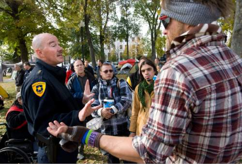 Al Hartmann  |  The Salt Lake Tribune  Salt Lake City Police Chief Chris Burbank, left,  reasons with members of the Occupy Salt Lake in Pioneer Park Friday afternoon November 11, 2011. He announced to occupiers that the camp would have to be dismantled and vacated by sundown on Saturday due to a death in the camp earlier on Friday morning and public safety concerns.