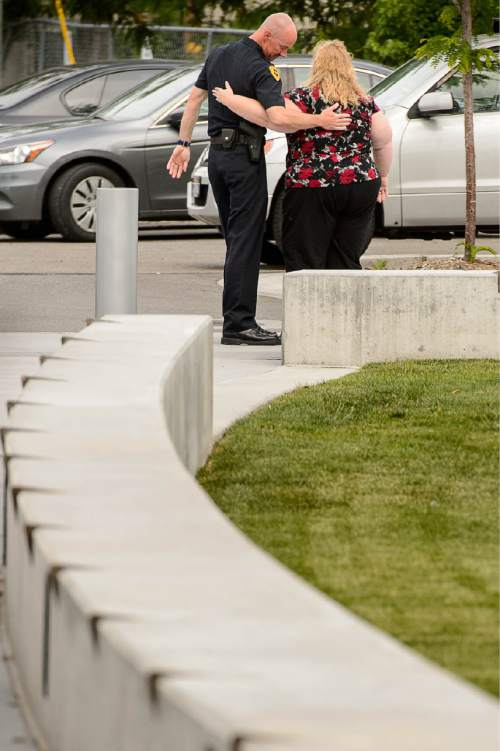 Trent Nelson  |  The Salt Lake Tribune Former Salt Lake City Police Chief Chris Burbank embraces an unidentified woman after speaking to reporters about his departure in front of the Public Safety Building in Salt Lake City Thursday June 11, 2015.