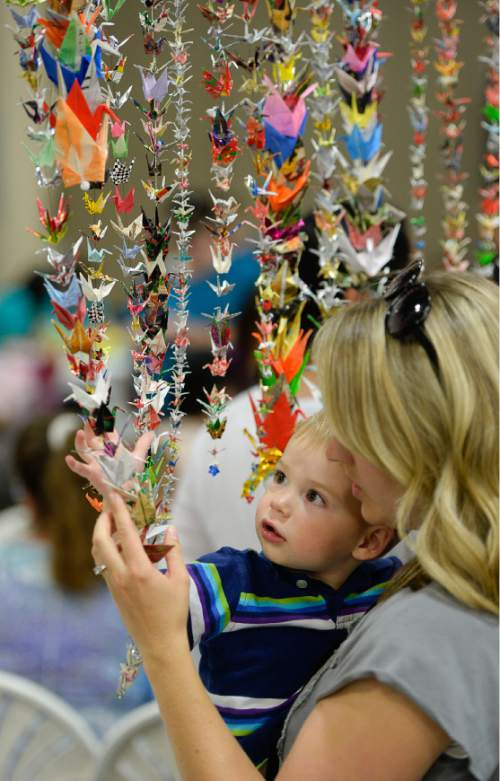 Francisco Kjolseth  |  The Salt Lake Tribune Erin Johnson of Riverton shows her son Elliot, 1, (cq) some of the 1000 cranes made from found paper by Ine Takenaka during the 38th Annual Asian Festival that celebrates Asian cultures with dance, music, food and more at the South Towne Expo Center on Saturday, June 13, 2015. This year the festival features Utah's Bhutanese, Cambodian, Chinese, Filipino, Indian, Indonesian, Japanese, Korean, Laotian, Taiwanese, Thai, Tibetan and Vietnamese communities.
