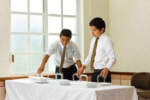 Courtesy  |  LDS Church  Young Latter-day Saint priesthood holders prepare the sacrament for Sunday worship services.