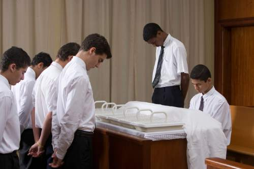 Courtesy  |  LDS Church  Young men administer the sacrament of bread and water to the congregation.