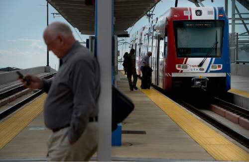 Scott Sommerdorf   |  The Salt Lake Tribune Riders board a UTA TRAX train on North Temple that's headed toward the airport, Thursday, June 11, 2015.