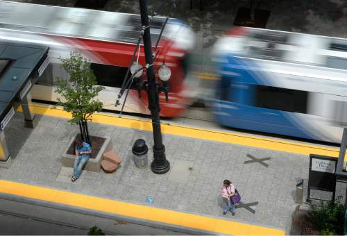 Scott Sommerdorf   |  The Salt Lake Tribune A UTA TRAX train blurs past riders waiting at the Gallivan Plaza Station in Salt Lake City, Thursday, June 11, 2015.