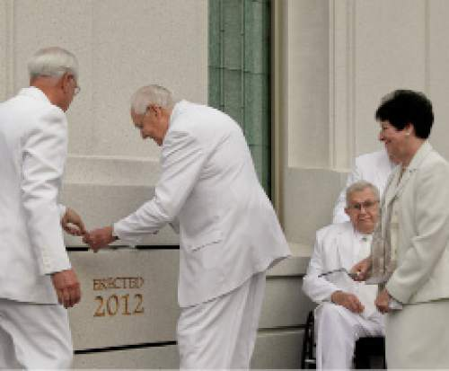 Courtesy  |  LDS Newsroom  Elder L. Tom Perry of the Quorum of the Twelve Apostles places mortar around the cornerstone of the Brigham City Utah Temple as his wife Barbara watches.