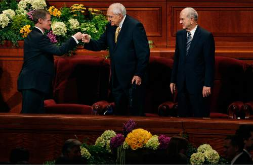 Scott Sommerdorf   |  Tribune file photo Elder David A. Bednar, left, fist bumps Elder L. Tom Perry with the empty chair of Elder Boyd K. Packer between them at the end of the afternoon session of the 183rd LDS General Conference, Sunday, April 7, 2013. Elder M. Russell Nelson is at the far right. Packer did not attend Sunday.