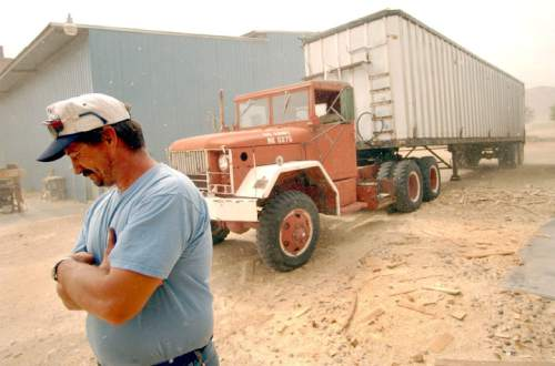 """Shane Steed, maintenance supervisor and one third owner of the Escalante sawmill closes his eyes as a wind storm kicks up saw dust near a truck being loaded with wood end-trims.  The mill which supplies numerous jobs to the local population re-opened recently after a 5-month closure, """"we opened with allot of help, it was almost surreal"""", replied Steed.       Francisco Kjolseth/The Salt Lake Tribune      09/25/2002"""