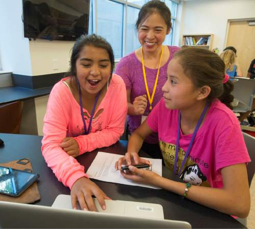 Rick Egan  |  The Salt Lake Tribune  Shianne Archuleta and Ashley Dias are assisted by instructor Helen Hu (center) while working on an app for their cellphones at the AWE+SUM Summer Girls Camp where eighth-grade girls participate in science and math and hands-on workshops during the four-day camp at Westminster, Friday, June 19, 2015.