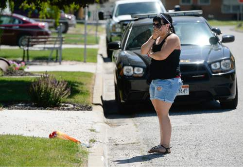 Francisco Kjolseth | The Salt Lake Tribune  A woman grieves after placing flowers at a home next to Roy High School that was the scene of an apparent Father's Day murder-suicide carried out by the husband and father.