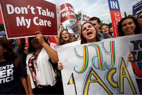 """Jessica Ellis, right, holds a sign that says """"yay 4 ACA,"""" as she and other supporters of the Affordable Care Act react with cheers as the opinion for health care is reported outside of the Supreme Court in Washington, Thursday June 25, 2015, in Washington. (AP Photo/Jacquelyn Martin)"""