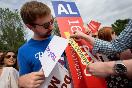 """Trent Seubert, left, holds a sign stating that 165,000 people would lose healthcare coverage, as the words """"lose healthcare"""" are covered over with a """"still covered"""" sticker outside the Supreme Court in Washington, Thursday, June 25, 2015, after the court decided that the without the Affordable Care Act (ACA) may provide nationwide tax subsidie. (AP Photo/Jacquelyn Martin)"""